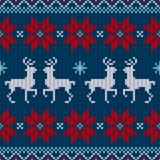 无缝的样式被编织的驯鹿和一品红红色白色蓝色 皇族释放例证