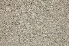 无缝的被点刻的米黄灰泥墙壁纹理背景 免版税库存照片