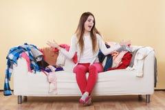 无能为力的妇女坐沙发在杂乱屋子家里 库存图片