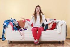 无能为力的妇女坐沙发在杂乱屋子家里 免版税库存照片