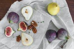 无花果、梨和pekan坚果在一个白色组织在一张木桌s上 免版税库存照片