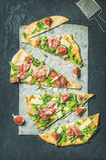 无花果、熏火腿、芝麻菜和贤哲在黑暗的背景的小面包干薄饼 库存图片