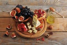 无花果和黑色葡萄在一个木碗 免版税库存图片