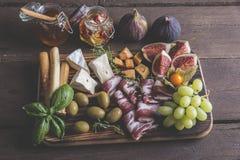 无花果,软制乳酪乳酪,熏火腿,橄榄,在黑暗的服务的葡萄上在土气木背景 库存图片