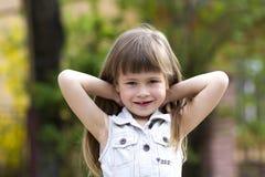 无袖的白色礼服的害羞地微笑入照相机的一个相当小长发白肤金发的学龄前女孩的画象反对弄脏 免版税图库摄影