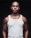 无袖衫的不易动情的年轻黑人 免版税库存照片