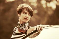 无袖衫的愉快的年轻时尚妇女在她的汽车旁边 免版税库存照片