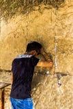 无边便帽的未认出的年轻犹太崇拜者祈祷在哭墙一个重要犹太宗教站点的 库存照片
