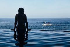 无限游泳池的妇女有海视图 免版税图库摄影