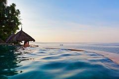 无限游泳池的妇女有海视图 免版税库存图片