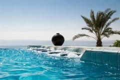 无限水池极可意浴缸,天蓝色的水 豪华生活方式,热带手段概念 免版税库存图片