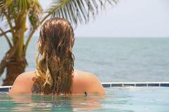 无限水池的妇女在海洋旁边 免版税库存图片