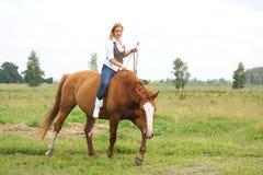 无鞍美丽的白肤金发的妇女骑乘马 库存照片