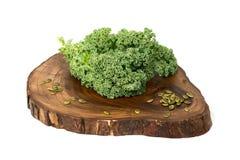 无头甘蓝叶子和南瓜籽在木切板 免版税库存图片