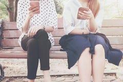 无兴趣片刻的两名妇女与在关系无积极性和使用新技术的室外,概念的巧妙的电话和smar 库存照片
