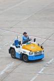 日产拖曳行李移动式摄影车运输的拖拉机在北京首都国际机场 免版税库存图片