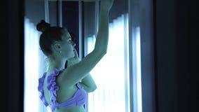 日光浴室 晒黑的紫色泳装的美丽的少女在垂直的日光浴室 影视素材