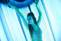 日光浴室 有非洲辫子的俏丽的女孩在东方舞蹈的一件礼服晒日光浴在垂直的sunbed 蓝色霓虹焕发 图库摄影