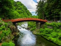 日光,日本- 2017年8月14日:红色古老桥梁,在Daiwa河在一多云天,世界的Shinkyo桥梁 免版税库存图片