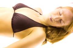 日光浴室晒黑的妇女 免版税图库摄影