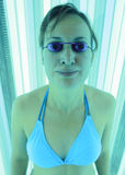 日光浴室晒黑的妇女 免版税库存图片