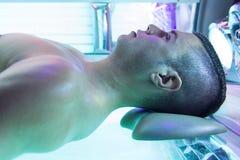 日光浴室的年轻肌肉人美容院的 库存图片