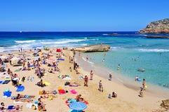 日光浴者在Cala Conta在圣安东尼奥,伊维萨岛海岛,温泉靠岸 免版税库存图片