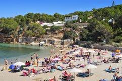 日光浴者在Cala Gracio在圣安东尼奥,伊维萨岛海岛, Sp靠岸 免版税图库摄影