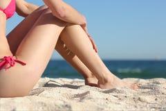 日光浴者妇女腿坐海滩的沙子 免版税图库摄影