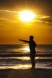 日出人指向日落的外形剪影 图库摄影