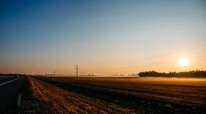 日出全景在种田在雾和柏油路的领域的 图库摄影