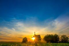 日出和一台老木风车 免版税库存图片