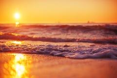 日出和发光在海洋挥动 图库摄影