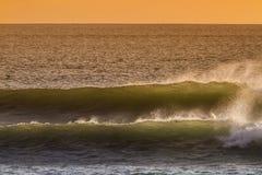 日出和发光在海洋挥动 库存图片