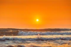 日出和发光在海洋挥动 免版税库存照片