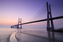 日出和桥梁在塔霍河在里斯本葡萄牙 库存图片