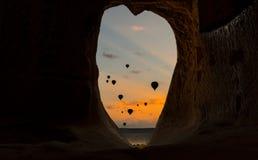 日出和观看从洞的孔的气球 免版税库存照片