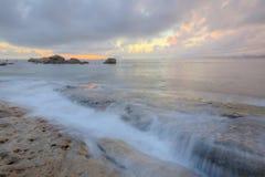 日出在与金黄阳光照亮的云彩的风雨如磐的天空下在多岩石的海滩 免版税库存照片