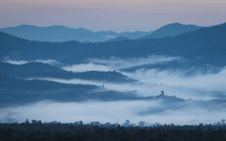 日出在有一个有薄雾的风景和小山的北泰国 免版税库存图片