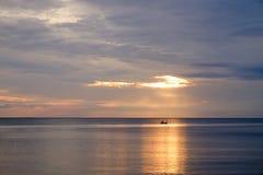 日出在海边,无形的太阳的天和在太阳下的一条小船 免版税库存图片