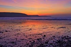 日出在淡水东部海滩湿沙子和小卵石反射了  免版税库存图片