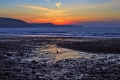 日出在淡水东部海滩湿沙子和小卵石反射了  库存图片