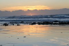 日出处于低潮中在南非的狂放的海岸的摩根海湾东伦敦 图库摄影