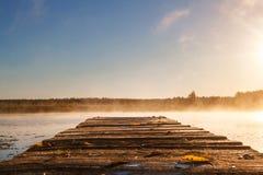 日出或日落在河有一个木码头的 雾ove 库存图片