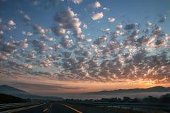 日出日落牧羊人覆盖街道高速公路太阳欧洲天空山雾 图库摄影