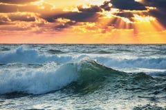 日出波浪 与深蓝天和太阳的五颜六色的海洋海滩日出发出光线 免版税库存图片