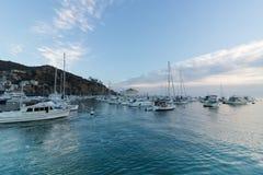 日出海景在看往有风船、在镇静海湾和游艇的赌博娱乐场的Avalon港口停泊的渔船 免版税库存照片