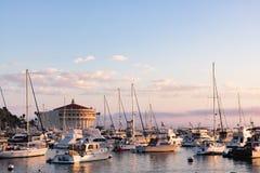 日出海景在看往有风船、在镇静海湾和游艇的赌博娱乐场的Avalon港口停泊的渔船 免版税库存图片