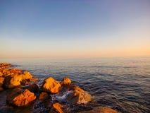日出海洋微风向岩石扔石头 库存图片