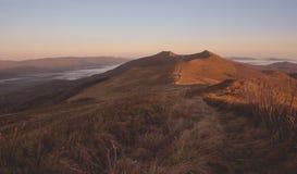 日出的一个褐色橙色山草甸与云彩反向在背景中在Bieszczady山 免版税库存照片